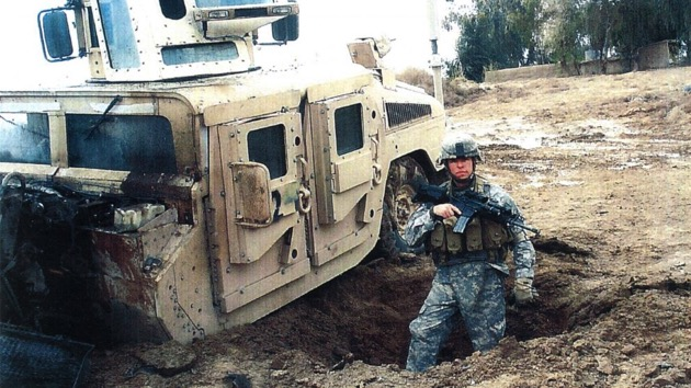 (U.S. Army)  Sgt. Travis Atkins stands next to his vehicle after it was damaged by an improvised explosive devise in Iraq during 2007.