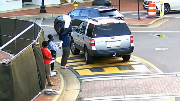 (Photo: Fayetteville Police Department) Surveillance video released by police shows an SUV driving around a traffic circle in Fayetteville, N.C., passing close to a group of Black Lives Matter protesters, May 7, 2021. Law enforcement officials said that lane is not currently open for traffic.